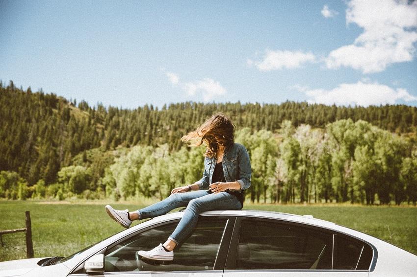 Las mujeres compran más autos que los hombres, mujer encima de un auto