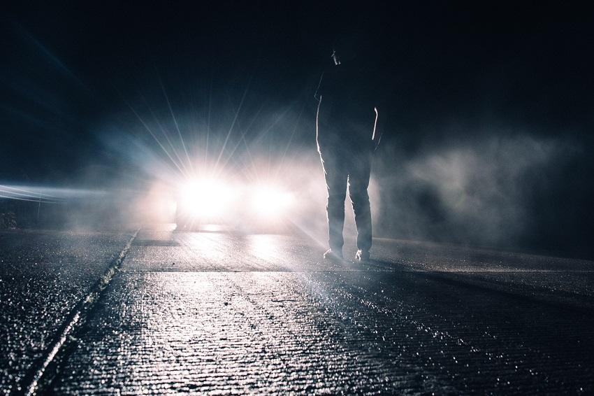 Colisiones en carretera, hombre iluminado por un auto